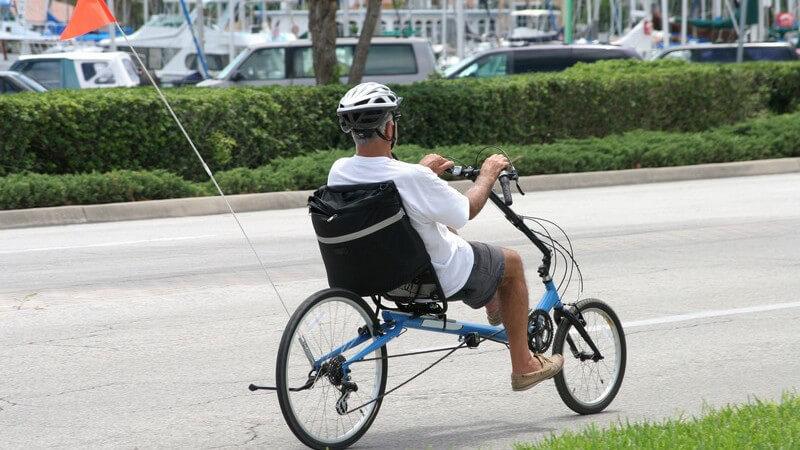 Rentner mit Helm auf Fahrrad in der Stadt