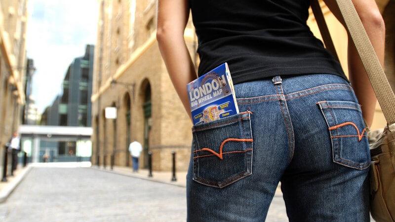 Hintern von junger Frau mit Bluejeans mit London-Stadtführer in der Gesäßtasche auf Straße in Stadt