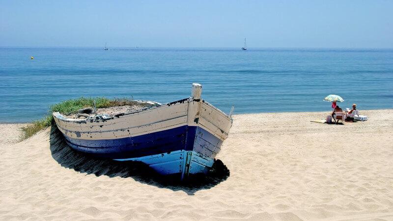 Altes blaues Boot am Strand von Andalusien, verwittertes Boot, mit Meer im Hintergrund und Strandgästen daneben