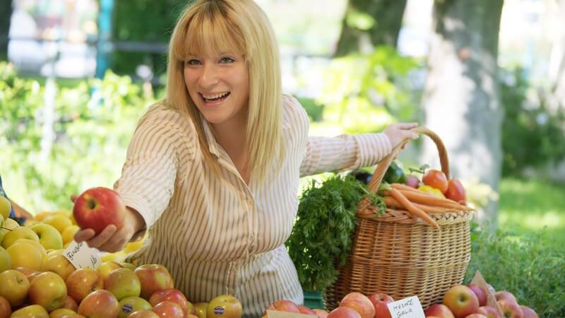 Blonde Frau mit Korb am Obststand kauft ein