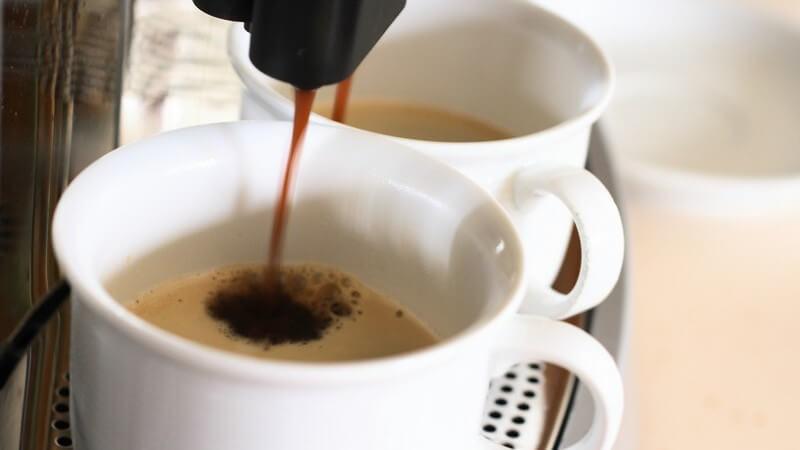 Kaffee läuft aus Kaffeemaschinen in Tassen