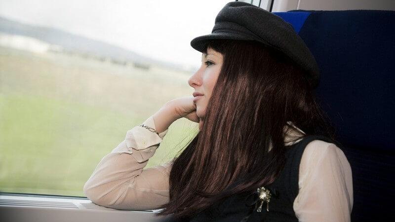 Junge Frau mit Hut schaut während einer Bahnfahrt aus dem Fenster