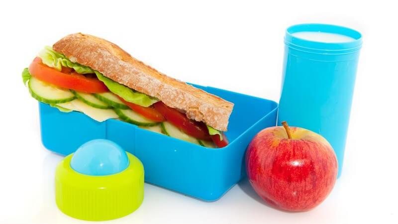 Lunchbox mit Baguette, Apfel, Becher mit Milch