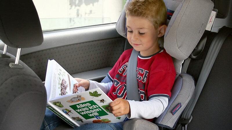 Kleiner Junge angeschnallt im Kindersitz im Auto schaut sich ein Buch an