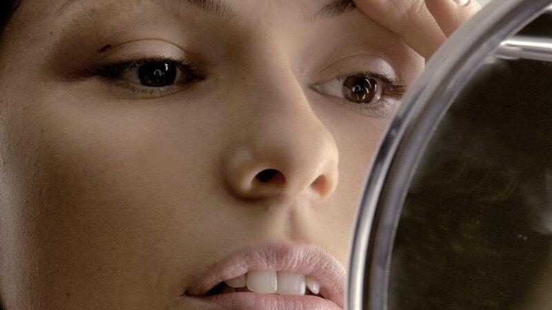 Junge Frau schaut in Handspiegel, streicht über Augenbraue
