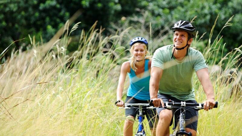Junges Paar mit Fahrradhelm beim Mountainbiking