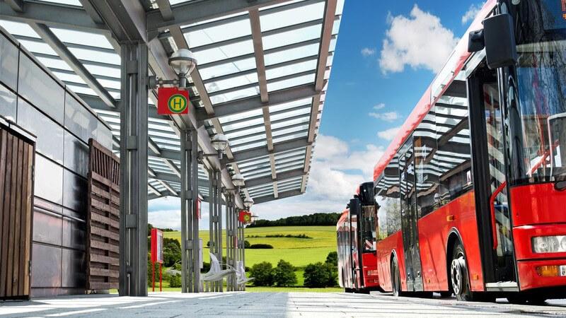 Linienbusse halten an Haltestellen von modernem Busbahnhof auf dem Land