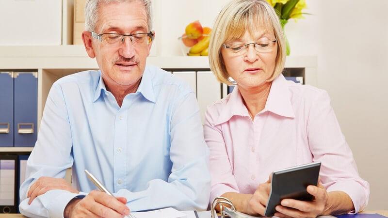 Älteres Paar sitzt am Tisch und macht die Steuererklärung, er mit Stift, sie mit Taschenrechner