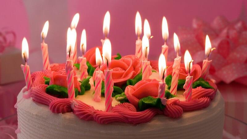 Weiß-rosa Geburtstagstorte mit Rosen und vielen Kerzen
