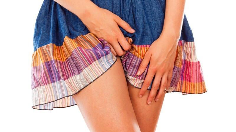 Frau in buntem Sommerkleid hat die Beine verschränkt und fasst sich an Unterleib und Oberschenkel