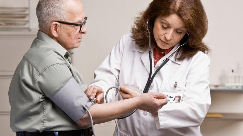 Ärztin misst Blutdruck bei älterem Mann