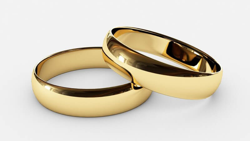 Nahaufnahme zwei goldene Eheringe auf weißem Hintergrund
