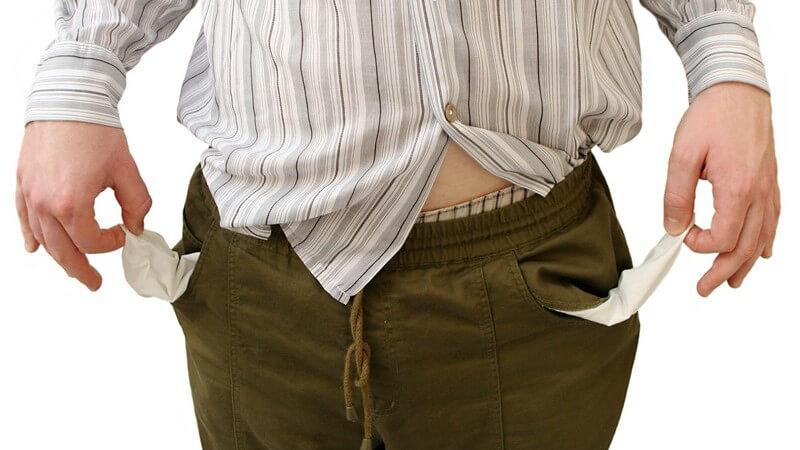 Schulden - Mann mit dem Hemd aus der Hose zeigt seine leeren Hosentaschen
