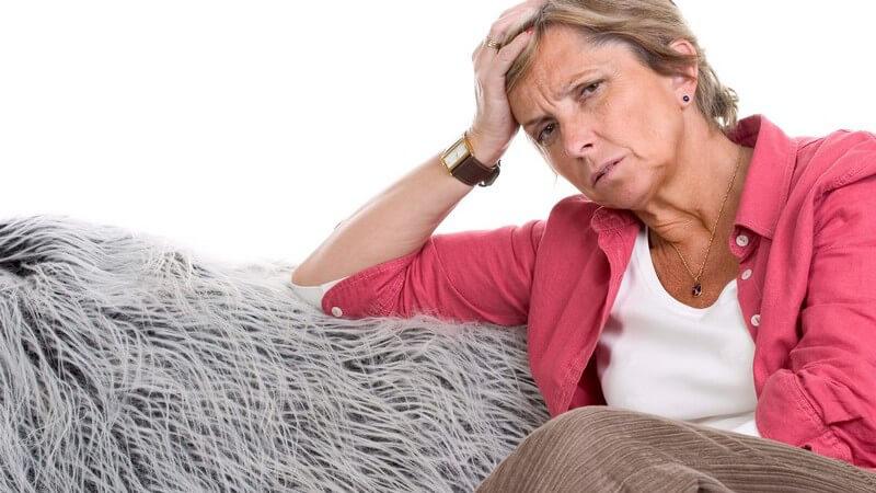 Ältere Dame in roter Bluse sitzt auf einer grauen Couch, den Kopf auf die rechte Hand gestützt