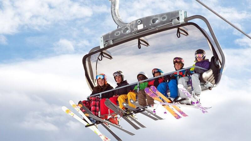 Mehrere Wintersportler mit Skiern sitzen im Sessellift