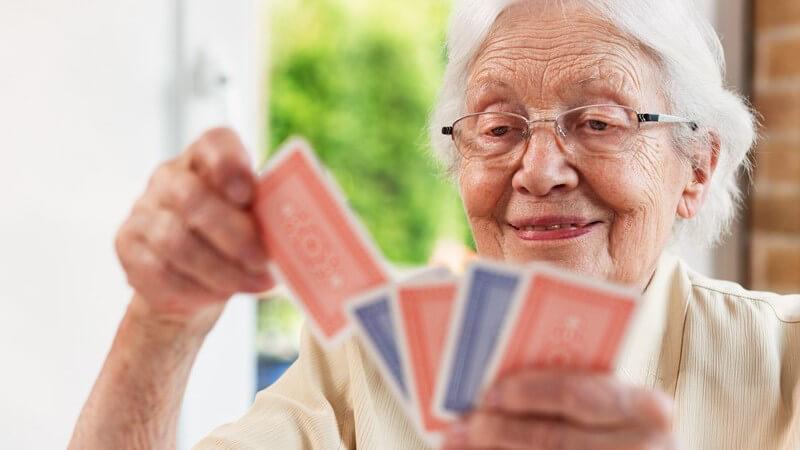 Alte Frau mit Brille sortiert ihre Spielkarten in der Hand