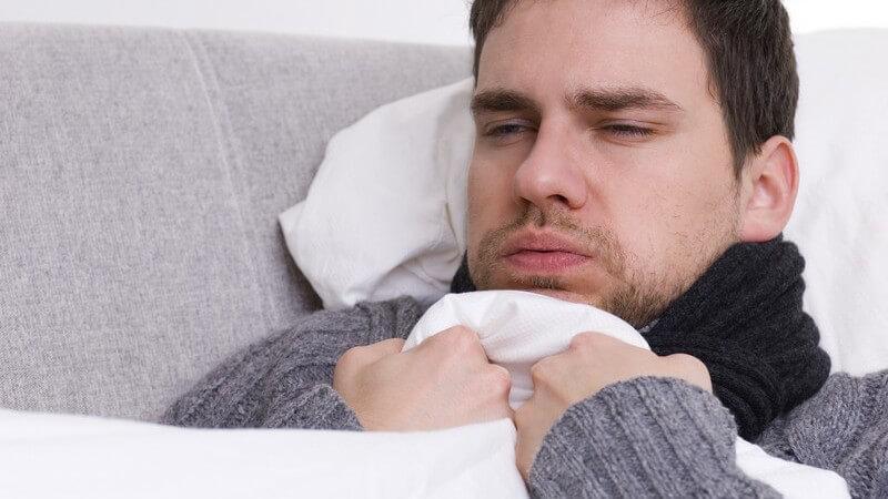 Erkälteter Mann mit Schal und Pulli liegt unter der Decke und friert