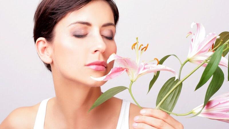Junge Frau riecht mit geschlossenen Augen an Orchidee