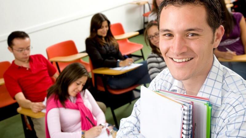 Studenten sitzen an Tischen, lernen, schreiben, Dozent oder Student steht vorne rechts mit Blöcken im Arm, Uni