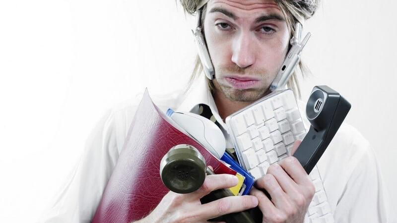 Gestresster und überforderter Mann mit mehreren Telefonen und Ordnern