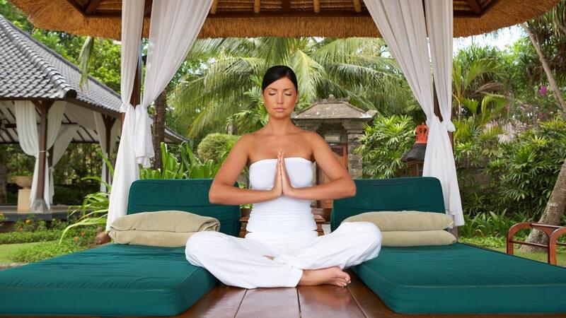 Frau sitzt in Pavillon in Natur in weißer Kleidung, Schneidersitz, Hände gegeneinander, Meditation oder Yoga, Palmen