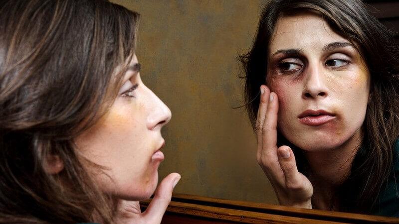Häusliche Gewalt: junge Frau mit Blutergüssen betrachtet Gesicht im Spiegel