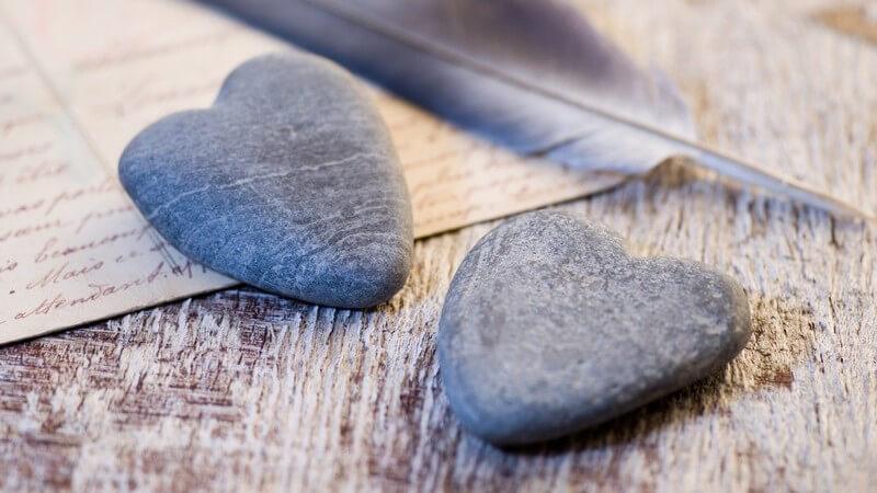 Nahaufnahme zwei Herzen aus Stein, im Hintergrund Postkarte, Schreib-Feder