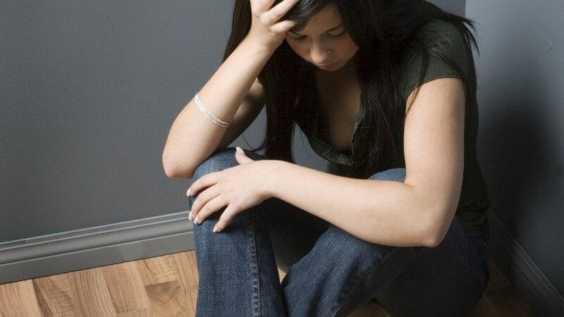 Junge depressive Frau sitzt in Zimmerecke, neben ihr Tabletten auf Boden