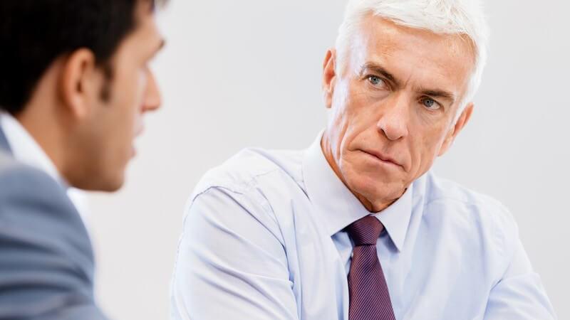 Älterer Geschäftsmann mit weißen Haaren und lila Krawatte guckt ernst und strend während Gespräch mit einem Mitarbeiter