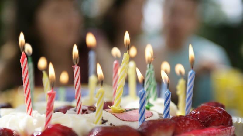 Torte mit Erdbeerhälften und vielen Kerzen, im Hintergrund Gäste