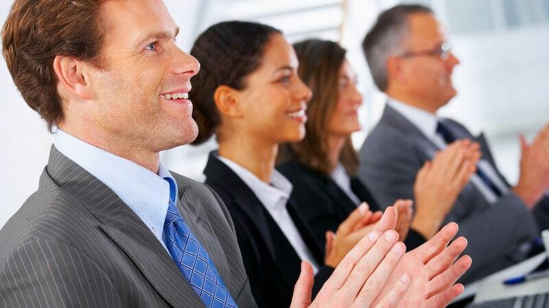 Seitenansicht vier Geschäftsleute schauen nach vorne und applaudieren