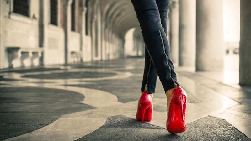 Frau spaziert in Lederhose und roten High Heels durch Venedig