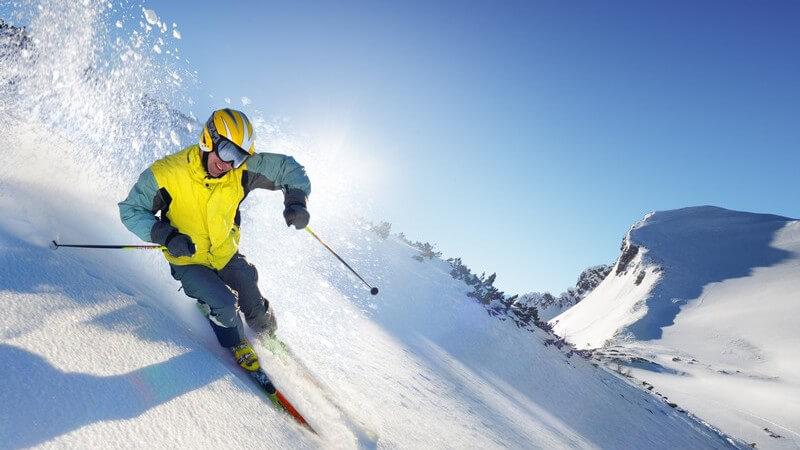 Skifahrer fährt steilen Hang in Bergen runter, blauer Himmel, Sonnenschein