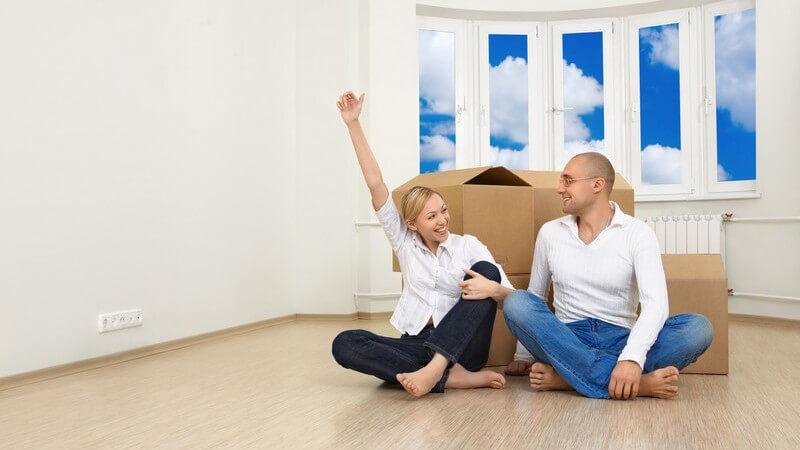 Junges Paar sitzt vor Kartons in neuer Wohnung