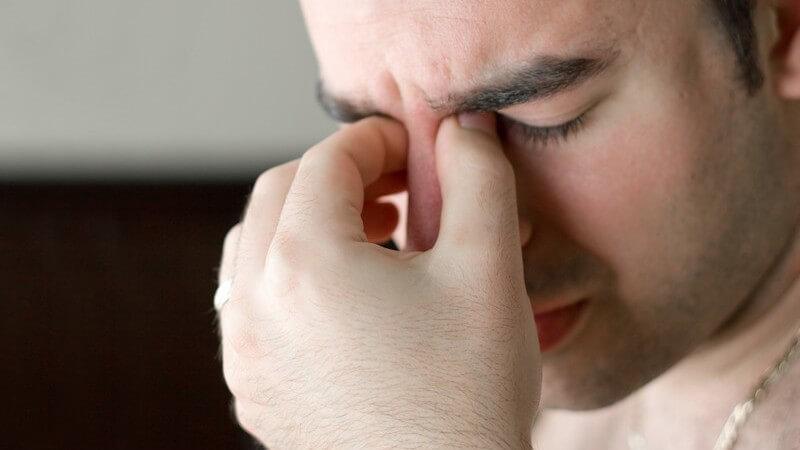 Erschöpfter Mann mit geschlossenen Augen fasst sich ins Gesicht