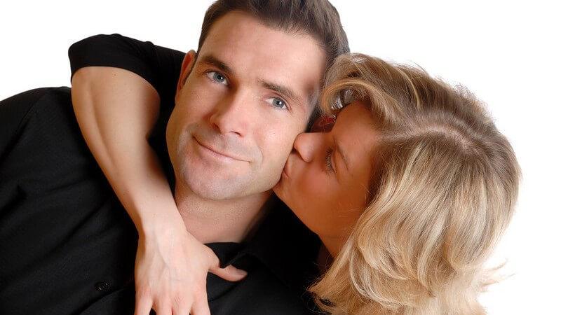 Blonde Frau umarmt ihren Partner von hinten und gibt ihm Kuss auf die Wange