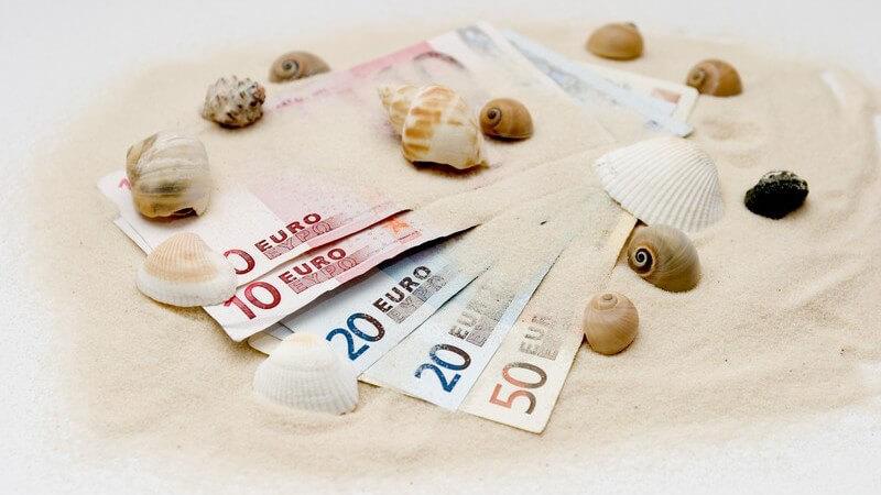 5 Geldscheine von 10-50 Euro liegen aufgefechert auf Sand mit Muscheln verziert