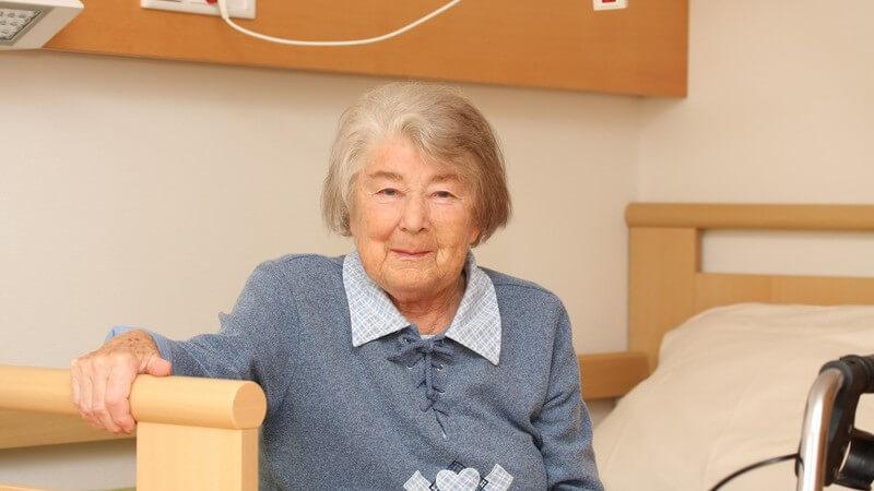 Alte Frau sitzt auf Bett im Heim und lächelt in Kamera