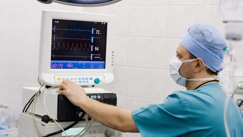 Mann in medizinischer Schutzkleidung kontrolliert mit der linken Hand einen Monitor mit medizinischen Messdaten