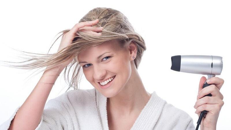 Blonde Frau im Bademantel föhnt sich die Haare mit Föhn