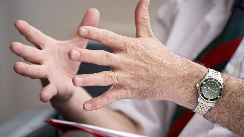 Zwei Hände von älterem Mann in Anzug, Ehering und Herrenuhr, bei Besprechung, Meeting o Diskussion mit Mappe auf Schoß