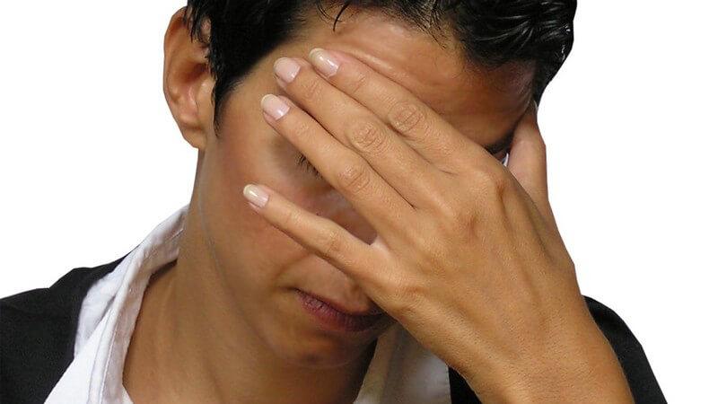 Kurzhaarige Frau hält sich linke Hand vor an Stirn vors Gesicht, Kopfschmerzen