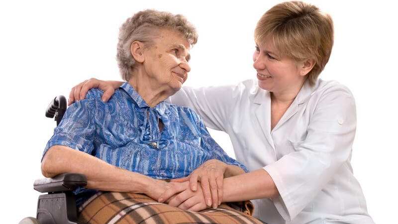 Alte Frau im Rollstuhl wird von Pflegerin betreut