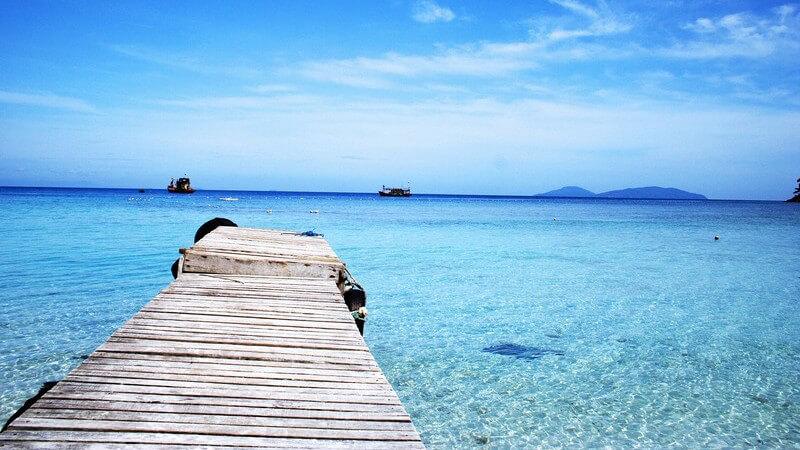 Pier oder Holzbootssteg ragt in azurblaues Meer hinein, klein im Hintergrund sind Schiffe oder Floße