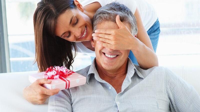 Frau hält Mann von hinten Augen zu, hält Geschenk in Hand, Überraschung
