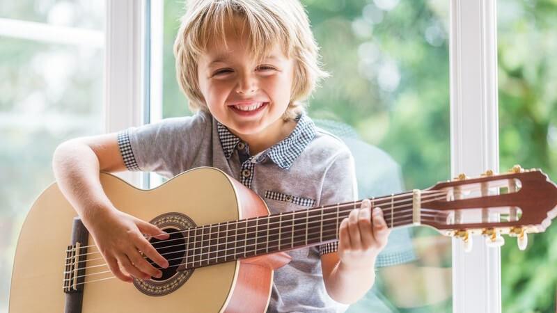 Blonder Junge sitzt an einem Fenster und spielt Akustikgitarre