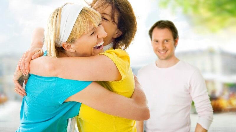 Zwei Freundinnen umarmen sich lachend, im Hintergrund lächelnder Mann