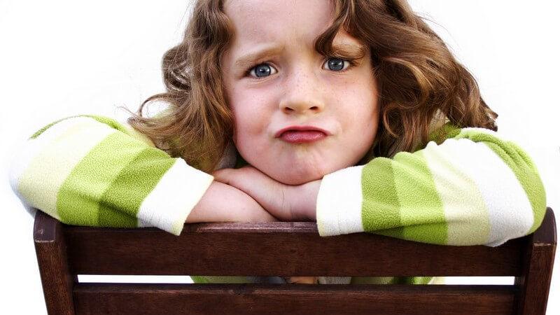 Kind mit brünetten Locken und grün-weißem Pullover schmollt, den Kopf auf den Handrücken