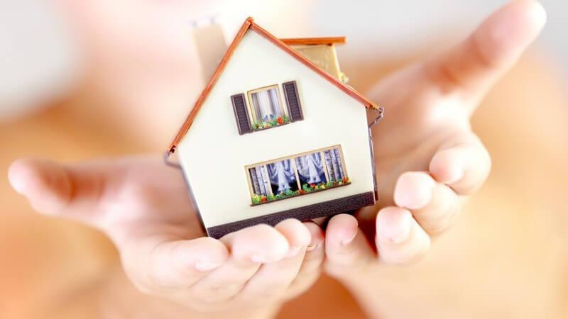 Nahaufnahme Kleines Modellhaus wird in offenen Händen gehalten