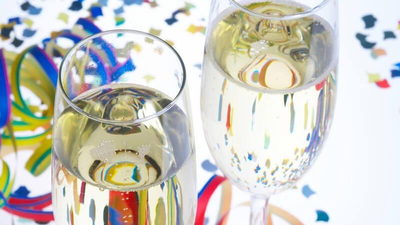 2 Sektgläser auf weißem Tisch mit Konfetti und Luftschlangen